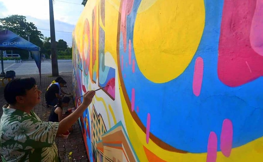 Mayor Jerry P. Treñas tried his hand at painting public art on the wall along bike lane in Brgy. Sambag in Jaro district Sunday.