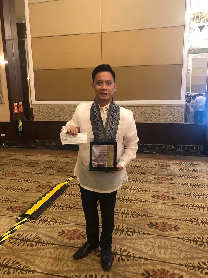 Punong Barangay Robert C. Niño Jr of Calumpang shows the plaque and cash award for winning the 2019 LTIA.