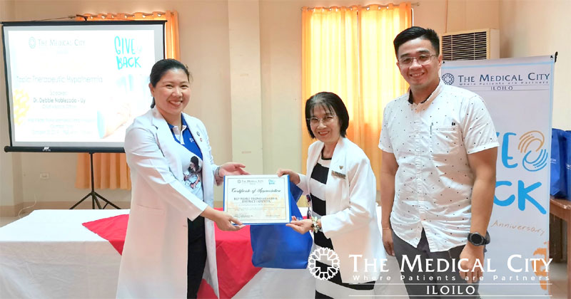 Rep. Pedro Trono Memorial District Hospital Head Nurse Josenia Custom receives the certificate from TMC Iloilo Chief Medical Officer Dr. Debbie Noblezada-Uy and TMC Iloilo Chief Marketing Officer Prince Celo.