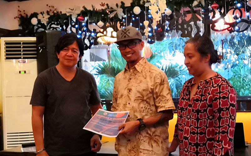 Committee members PG Zoluaga (left) and Leny Ledesma (right) award Vladimir Guanzon as winner of Iloilo Summer Arts Festival logo making contest.