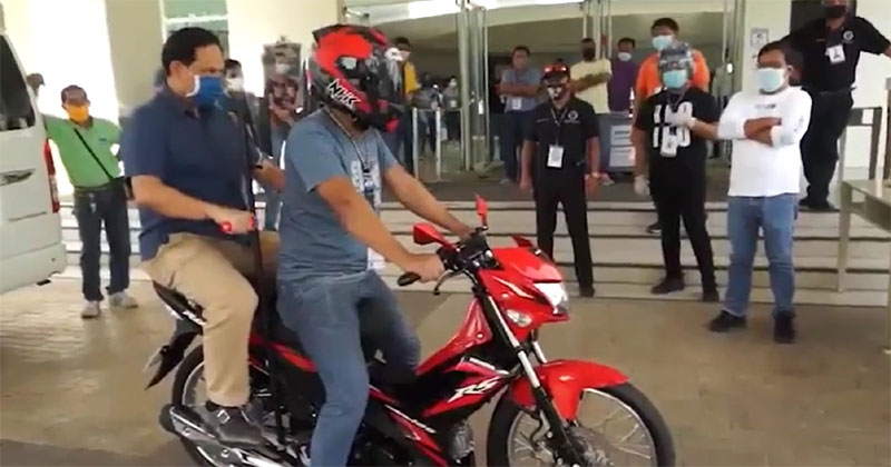 Gov. Art Defensor Jr trying out the motorcycle with safety innovation for physical distancing.