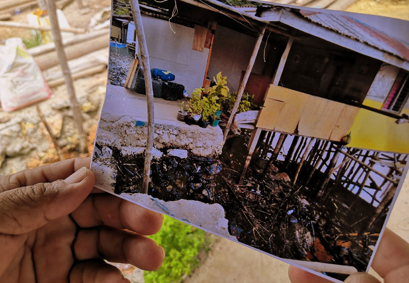 Domingo Fruto showing a photo of the bunker fuel sticking on rocks under his house along the shoreline of Brgy. Hoskyn in Jordan, Guimaras.