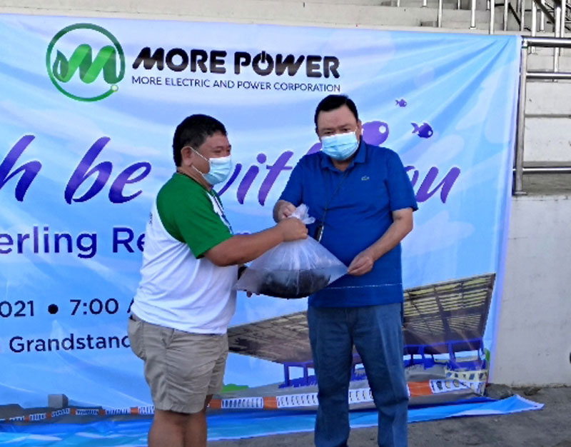 MORE Power President Roel Z. Castro turns over the juvenile fishes to Mayor Jerry P. Trenas.