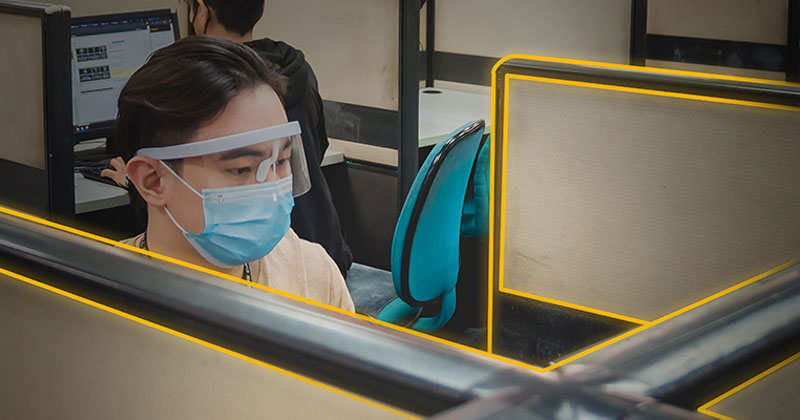 Office worker with mask and faceshield.